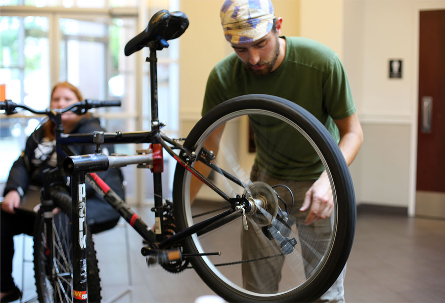 A repair cafe volunteer fixes a bike